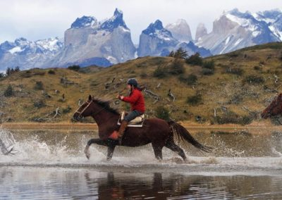 Horse-race-in-a-lake.-Explorers-enjoying-the-wilderness-of-Patagonia-mgv1c3xfdee0e9k3qdy0r3p5muk09hk03kt8klsdqg